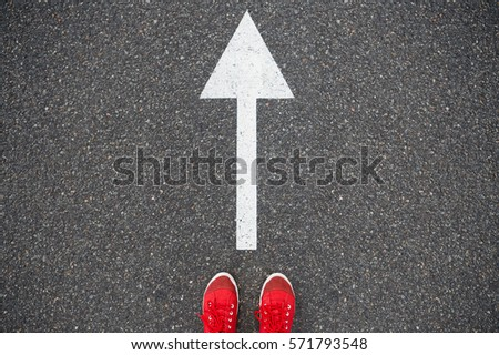 Sneakers on the asphalt road with drawn direction arrow #571793548