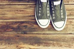 sneakers on wooden deck.