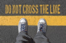 Sneakers standing on the yellow line. Crime and danger concept.
