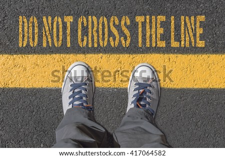 Sneakers standing on the yellow line. Crime and danger concept. #417064582