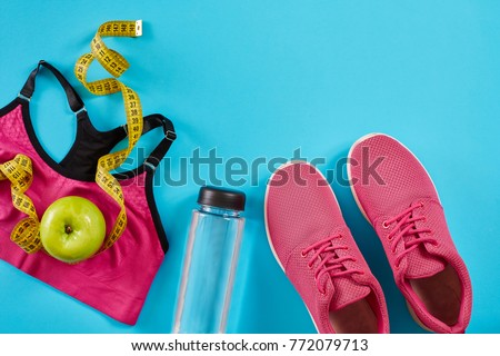 Sneakers with measuring tape on cyan blue background. Centimeter in yellow color, pink sneakers, female sport top and bottle of water, copy space. #772079713