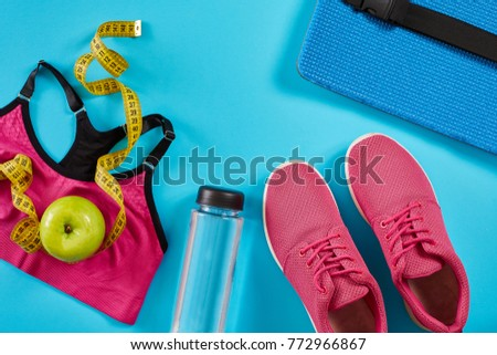Sneakers with measuring tape on cyan blue background. Centimeter in yellow color, pink sneakers, female sport top and bottle of water, copy space. #772966867