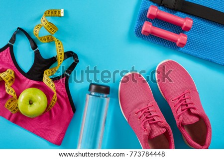 Sneakers with measuring tape on cyan blue background. Centimeter in yellow color, pink sneakers, female sport top and bottle of water, copy space. #773784448