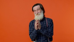 Sneaky cunning mature bearded grandfather with tricky face gesticulating and scheming evil plan, thinking over devious villain idea, cunning cheats, jokes and pranks. Senior man on orange background