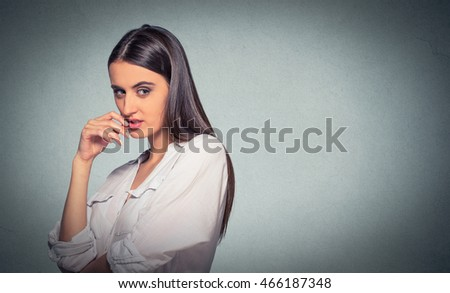 sneaky, sly, scheming young woman plotting something isolated on gray background. Negative human emotion facial expression feeling
