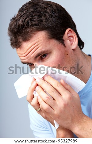 Sneezing man having cold. On a gray background. - stock photo