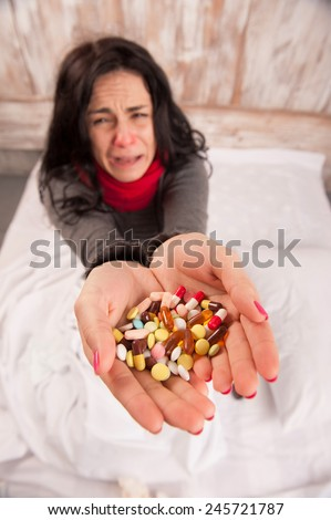 Sneezing woman. Top view image of young sick woman sneezing while sitting on bed with pills and tissues against wooden wall