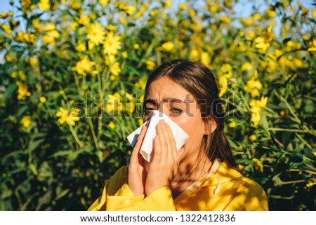 Sneezing young girl with nose wiper among blooming flowers in park. Young woman got nose allergy, flu sneezing nose. The girl suffers from pollen allergy during flowering and uses napkins. Allergy