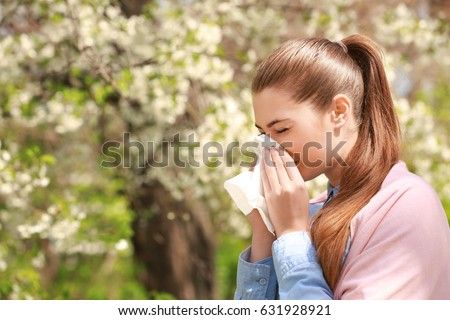 Sneezing young girl with nose wiper among blooming trees in park ストックフォト ©