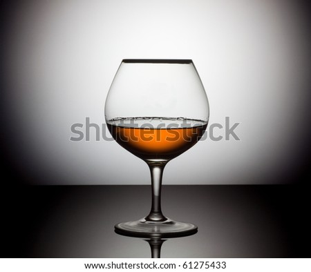 Snifter glass of cognac over circle white and black background