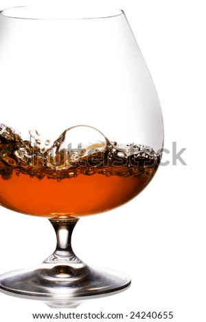 Snifter glass of splash cognac on white background.
