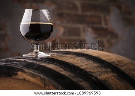 Snifter glass with black stout beer standing on an oak barrel in a cellar Stock photo ©