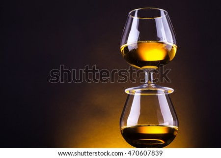 Snifter glasses with brandy stacked on top of each other over a yellow lit background #470607839