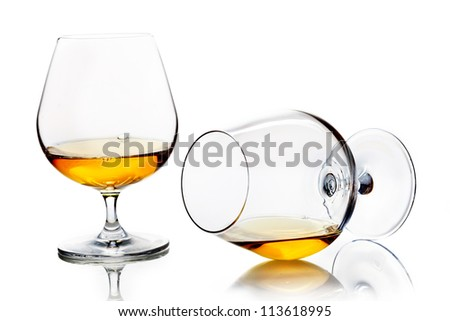Snifters with brandy or cognac, one standing upright and one angled towards the camera lying on its side on a white studio background