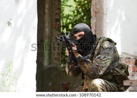 Sniper in black mask aiming for his victim via optical scope - stock photo