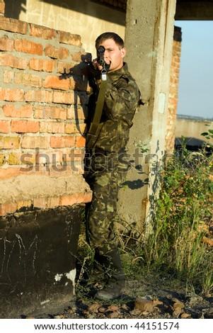 sniper in camouflage ambushing behind brick wall