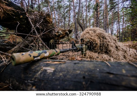 Sniper in camouflage suit is hiding and aiming behind a tree/Camouflaged sniper lying in forest and aiming through his scope