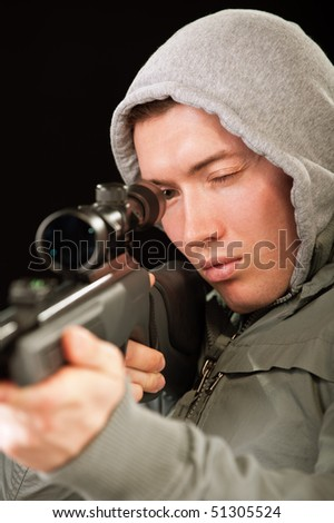 Sniper in hood aims at rifle optical sight