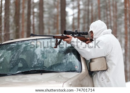 Sniper in white camouflage on jeep at winter forest.