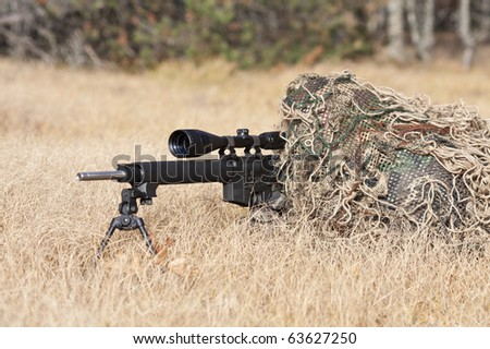 sniper laying on the ground covered in a ghille suite tall grass and trees in the background