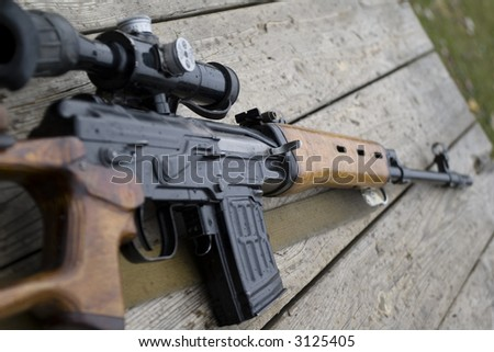 Sniper rifle gun with optical sight  laying on wooden desk close-up