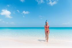 Snorkel bikini woman having fun coming from swimming in cristalline ocean water snorkeling in the Caribbean. Summer beach travel lifestyle.