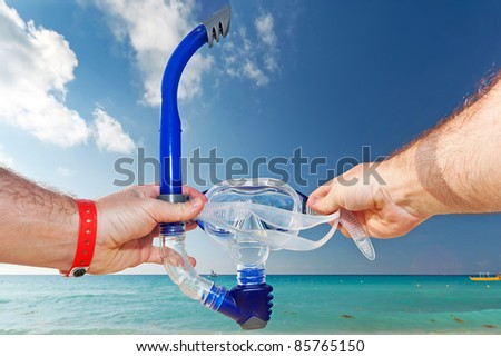 Snorkel equipment in hands against beach and sky