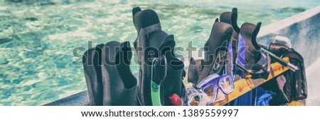 Snorkel fins and mask sets on cruise excursion activity snorkeling from boat in Tropical summer vacation travel destination panoramic banner. #1389559997