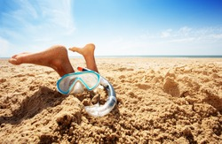 Snorkel, mask and feet of a boy in sand on beach