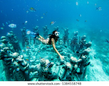 Snorkel woman swimming in a turquoise ocean under the flooded statues. Life tours and outdoor water sports. The concept of free diving. #1384558748