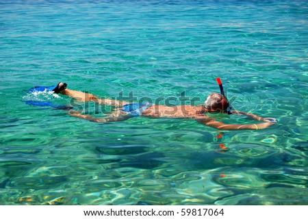 Snorkeler is taking underwater pictures