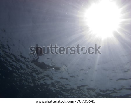 Snorkeler on the surface taken from underwater with a big sunshine