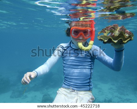Snorkeling child underwater with giant clam
