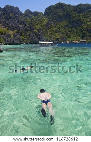 Snorkeling man in clear sea, Palawan, Philippines.