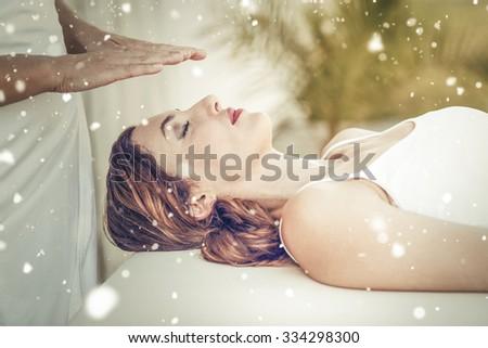 Snow against calm woman receiving reiki treatment