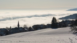 Snow and a village in front of a sea of fog in the Jura Mountains (Switzerland)