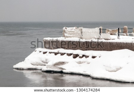 Snow and ice covered jetty set against gloomy winter overcast sky.