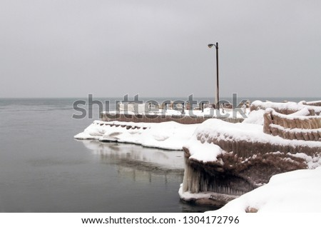 Snow and ice covered jetty with street light set against gloomy winter overcast sky.