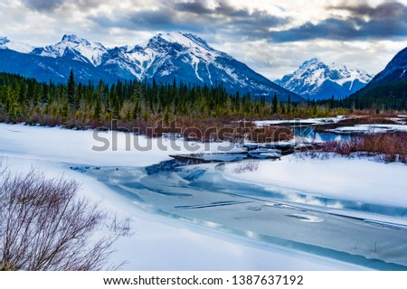 Snow and ice covered Kananaskis River surrounded by trees, shrubs with snow covered Mount Kidd and Mount McDougall under a moody cloud filled sky.