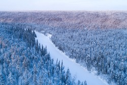 Snow and ice covered river valley surrounded with a wintery taiga forest in Oulanka National Park, Finnish nature.