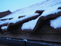 Snow and ice covers roof tiles on a barn