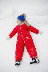 Snow Angel. Boy in winter red clothes lies in the snow. Selective focus, blurred background.