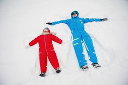Snow Angel. Dad and son in winter red and blue clothes lie in the snow. Selective focus, blurred background.
