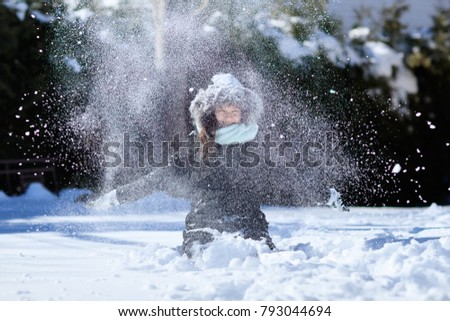 Snow blowing by a pretty girl. Cute girl in winter clothes playing outdoors on snow. Active leisure with children in winter on cold days. Snow juggling in white landscape