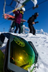Snow, blue sky. Snowing mountains and skiing man  in ski google reflection