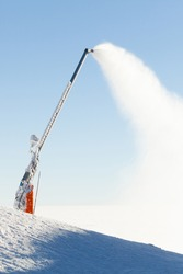 Snow cannon making artificial powder at the top of a ski slope