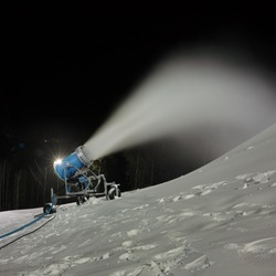 Snow cannon spraying artificial snow on a ski slope, night panorama at long exposure, closeup.