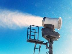 Snow cannon sprays artificial snow against a bright blue sky