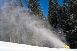 Snow cannons make snow surface. Snow cover for the winter season at the ski resort. Snow making machine