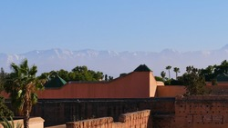 Snow-capped Atlas Mountains above the mist viewed from historic El Badi Palace with loam constructions and palm trees in the historic center (Medina) of Marrakesh, Morocco on sunny day with blue sky.